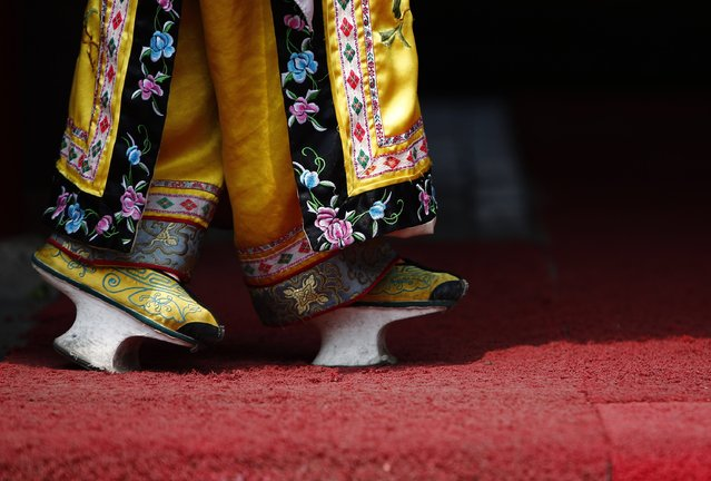 A restaurant promoter wearing a pair of chopines, traditional Chinese footwear, waits for customers in Beijing May 8, 2014. (Photo by Kim Kyung-Hoon/Reuters)