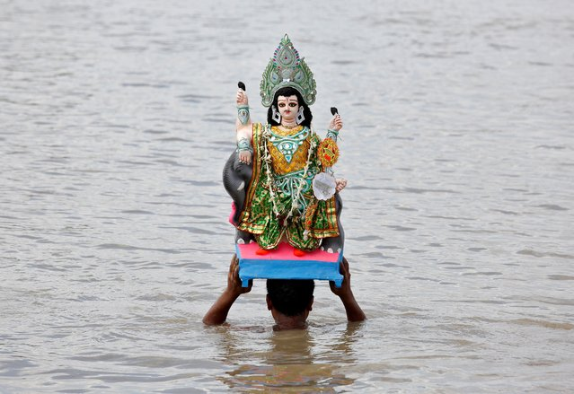 A devotee carries an idol of Lord Vishwakarma, the Hindu deity of architecture and machinery, to immerse it into the waters of the river Ganges in Kolkata, India, September 19, 2019. (Photo by Rupak De Chowdhuri/Reuters)