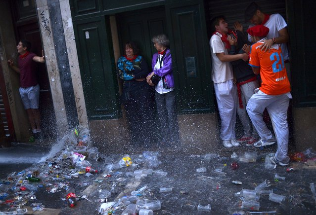 Revellers squeeze into doorways to avoid water jets from street cleaners on the seventh day of the San Fermin festival in Pamplona, northern Spain, July 12, 2015. (Photo by Vincent West/Reuters)
