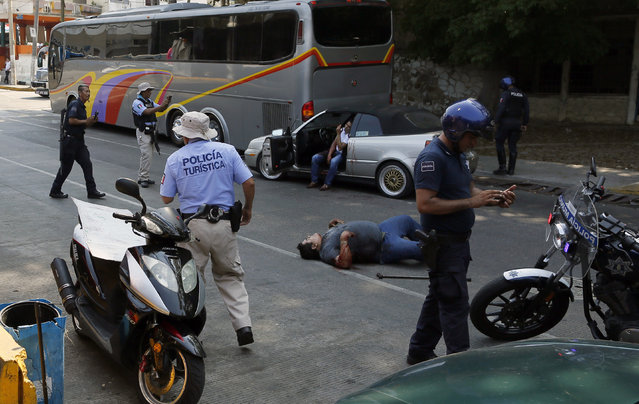 A wounded man lies on the ground and a second one sits in his car waiting for assistance as police arrive to the scene of a shooting near Caleta beach in Acapulco, Mexico, Friday, May 13, 2016. The city of Acapulco and Guerrero state in general have experienced a wave of violence attributed to warring drug gangs. On Saturday Mexican authorities say three men were gunned down, killing all three, in a tourist-hotel quarter of the Pacific resort city. (Photo by Enric Marti/AP Photo)
