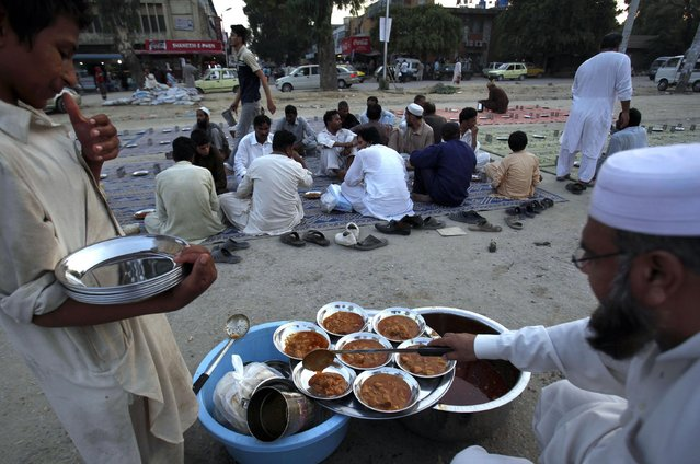 Pakistani volunteers prepare food for devotees to break their Ramadan fast in Islamabad, Pakistan, Sunday, July 5, 2015. (Photo by Anjum Naveed/AP Photo)