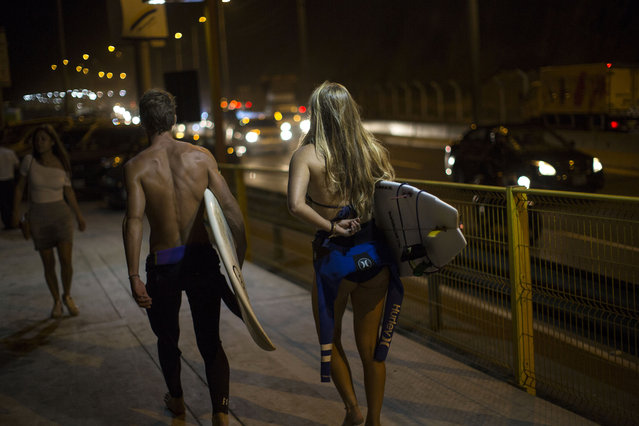 In this Feb. 17, 2017 photo, surfers walk to La Pampilla beach in Lima, Peru. Night surfing apparently came about in Lima because of a dispute with the capital municipality that in 2015 increased the width of a road that runs along the coast. The surfers protested the construction for months by camping on the asphalted beach area, but in the end the municipality prevailed, with support from the police. At the end of 2016, perhaps to win over the surfers, Lima's mayor set up beach lights that allows for night surfing. (Photo by Rodrigo Abd/AP Photo)