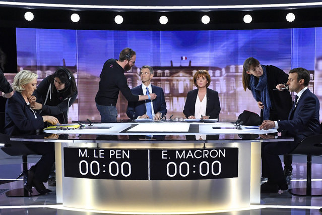 French presidential election candidate for the far-right Front National party, Marine Le Pen, left, French journalist Christophe Jakubyszyn, 2nd left, French journalist Nathalie Saint-Cricq, 2nd right, and French presidential election candidate for the En Marche ! movement, Emmanuel Macron, right, get prepared by technicians prior to the start of a live broadcast face-to-face televised debate in La Plaine-Saint-Denis, north of Paris, France, Wednesday, May 3, 2017 as part of the second round election campaign. Pro-European progressive Emmanuel Macron and far-right Marine Le Pen are facing off in their only direct debate before Sunday's presidential runoff election. (Photo by Eric Feferberg/Pool Photo via AP Photo)