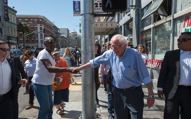 Democratic presidential candidate Bernie Sanders shakes hands with a man holding a beer while taking a walk through San Francisco, California on May 18, 2016. (Photo by Josh Edelson/AFP Photo)