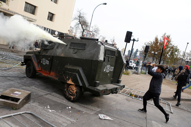 A demonstrator uses a stick against a riot police vehicle during an unauthorized march called by secondary students to protest against government education reforms in Santiago, Chile, May 26, 2016. (Photo by Ivan Alvarado/Reuters)