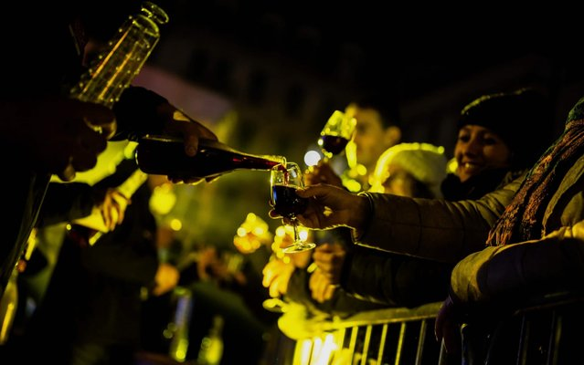 """People taste the new wine during the official start of the """"Beaujolais Nouveau"""" edition in the streets of Lyon, central-eastern France, on November 20, 2019. (Photo by Jeff Pachoud/AFP Photo)"""