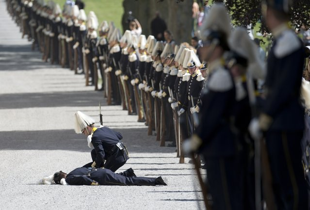 A soldier from the royal guard lies on the ground after fainting during guests arrival for Princess Leonore's christening on June 8, 2014 at the Royal Chapel in Drottningholm's royal palace near Stockholm. (Photo by Jonathan Nackstrand/AFP Photo)