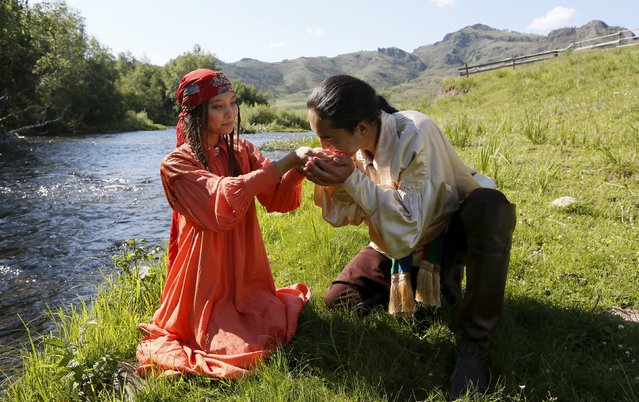 A man drinks water from hands of a woman as members of national folklore and ethnographic groups participate in the reconstruction of daily life and traditional holidays celebrated by indigenous population of the Republic of Khakassia during a demonstration for visitors at a museum preserve outside Kazanovka village, southwest of the city of Abakan, Russia, July 24, 2015. (Photo by Ilya Naymushin/Reuters)