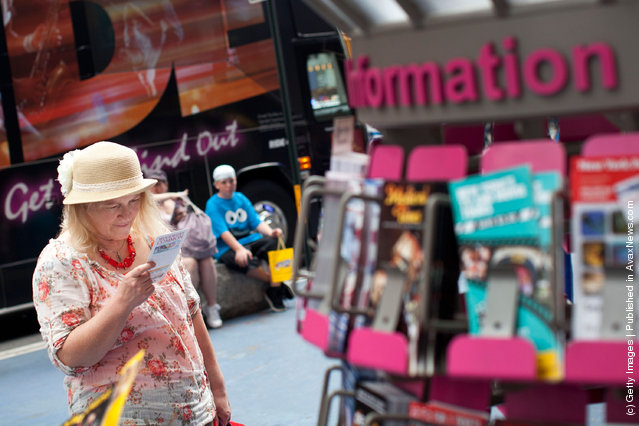 A woman reads a flyer from an information booth in Times Square on March 23, 2012 in New York City
