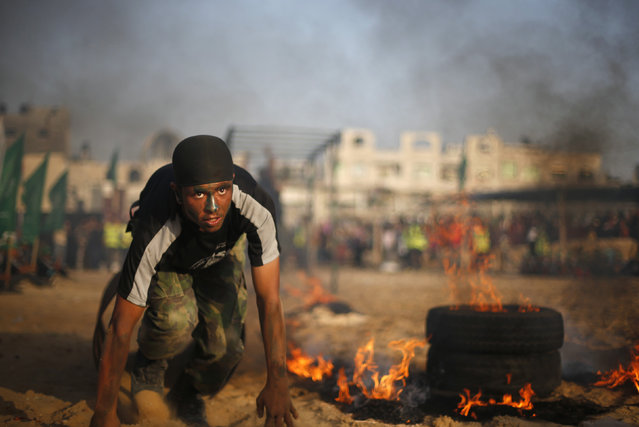 """A Palestinian boy crawls next to burning tyres during a military-style graduation ceremony at Fajer Al-Entesar (dawn of victory) summer camp, organized by the Hamas movement, in Gaza City June 19, 2014. Hamas stages dozens of military-style summer camps for young Palestinians in the Gaza Strip to prepare them to """"confront any possible Israeli attack"""", organisers said. (Photo by Mohammed Salem/Reuters)"""