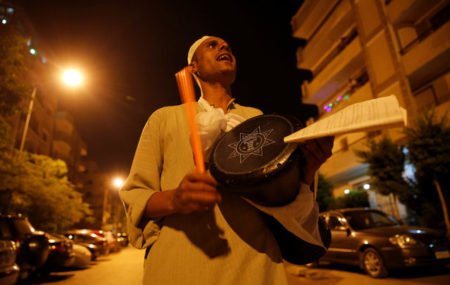El Mesaharty, Hussien, 40, wakes up residents for their pre-dawn meals during the first day of Ramadan in Cairo, Egypt June 6, 2016. (Photo by Amr Abdallah Dalsh/Reuters)