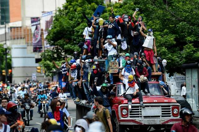 Venezuelan students and other opposition demonstrators protest outside the National Telecommunications Commission (CONATEL) to demand an end to media censorship in the country, in Caracas on June 9, 2017. Clashes at daily protests by demonstrators calling for Maduro to quit have left 66 people dead since April 1, prosecutors say. (Photo by Federico Parra/AFP Photo)