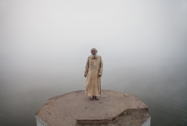 """""""The Fog"""". Submerged in fog, a holy man stands on a raised platform above the Ganges River in Varanasi. Photo location: Varanasi, India. (Photo and caption by Zack Vitiello/National Geographic Photo Contest)"""