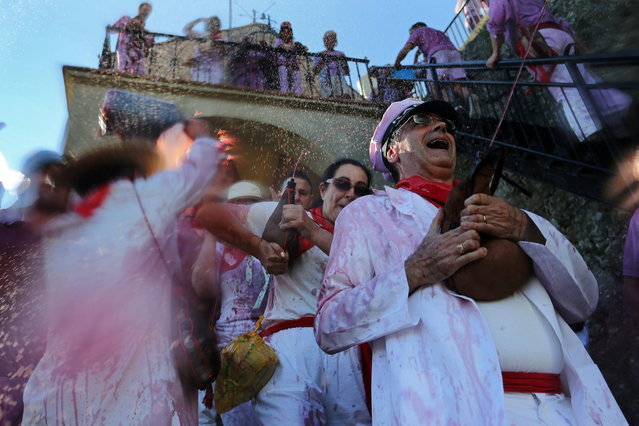 """Revelers spray wine as they take part in the """"Battle of Wine"""" (La batalla del vino de Haro), a wine fight, during the Haro Wine Festival, in Haro, in the northern province of La Rioja on June 29, 2014. More than nine thousand locals and tourists threw around 130.000 litres of wine at each other during the Haro Wine Festival, according to local media. (Photo by Cesar Manso/AFP Photo)"""