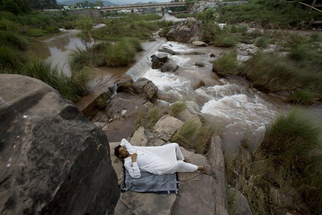 A Pakistani man takes a nap at waterside during a hot afternoon in Islamabad, Pakistan, July 30, 2015. (Photo by B. K. Bangash/AP Photo)