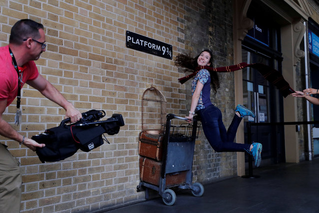 "A woman poses for a photograph with the Harry Potter trolley at Kings Cross Station, in London, Britain June 26, 2017. The first Harry Potter book, ""Harry Potter and the Philosopher's Stone"" was first published 20 years ago. (Photo by Eddie Keogh/Reuters)"
