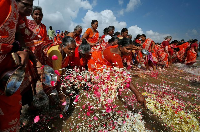 Women scatter flower petals in the waters of the Bay of Bengal during a prayer ceremony for the victims of the 2004 tsunami on the 15th anniversary of the disaster, at Marina beach in Chennai, December 26, 2019. (Photo by P. Ravikumar/Reuters)
