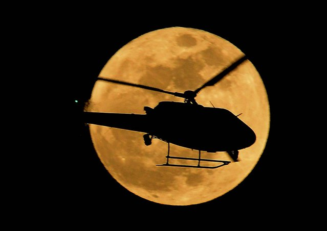 LAPD chopper flies in a foregraund of the Super Moon in Los Angeles, California on May 05, 2012