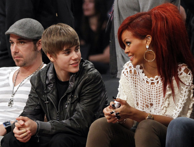 Justin Bieber talks with Rihanna as they sit courtside during the 2011 NBA All-Star game in Los Angeles. (Photo by Danny Moloshok/Reuters)