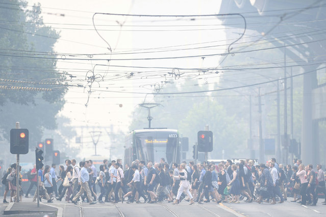 Morning commuters endure a smoke haze from bushfires in Melbourne, Australia on January 14, 2020. (Photo by Erik Anderson/Reuters)