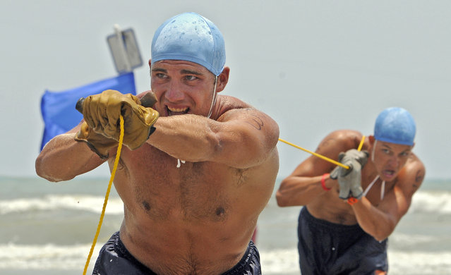 "North Myrtle Beach lifeguards Luke Fender, left, and Dylan McCann drag the rope back in during the Landline Rescue Race in the South Atlantic Lifesaving Association regional competition Wednesday, July 9, 2014, in North Myrtle Beach, S.C. In this event the swimmer with the rescue buoy swims out to another team member who is the ""victim"", then two other team members use the rope to pull in the victim and the rescue swimmer. (Photo by Charles Slate/AP Photo/The Sun News)"