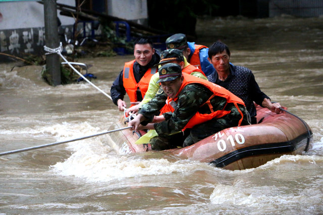 Rescuers grab a rope to prevent a raft carrying residents from being flushed away as residents are evacuated from a flooded area in Jiujiang, Jiangxi Province, China, June 19, 2016. (Photo by Reuters/Stringer)