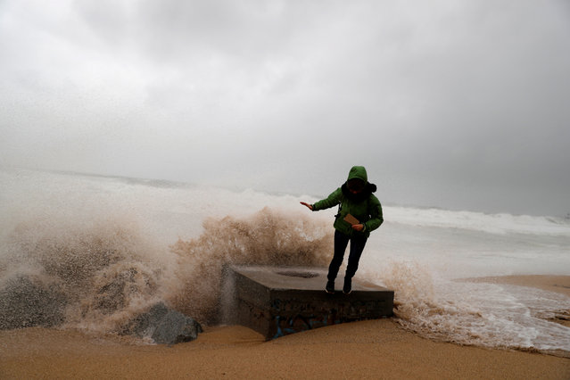 """A woman is pictured during the storm """"Gloria"""" on Maresme coast in Badalona, near Barcelona, Spain, January 21, 2020. (Photo by Nacho Doce/Reuters)"""