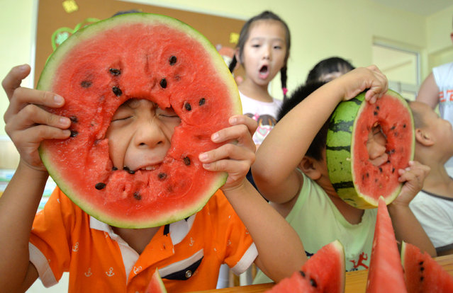 "Children eat watermelons to meet the ""beginning of autumn"" at a kindergarten in Handan, China on August 7, 2015. Chinese tradition to eat watermelons or peaches before that day symbolises ""biting away summer"". The solar term 'beginning of autumn' falls on 8 August this year. (Photo by Xinhua/REX Shutterstock)"