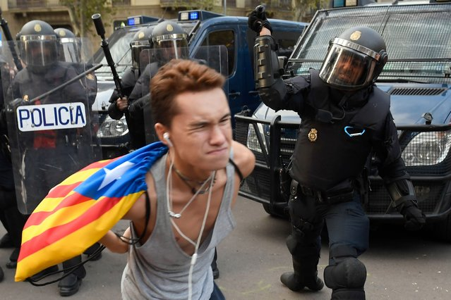"""A Spanish national police officer uses his club to hit a protester during a demonstration called the Catalan pro-independence left youth group """"Arran"""" on October 19, 2019 in Barcelona, a day after nearly 200 people were hurt in another night of violent clashes in Catalonia. The deterioration came on the fifth consecutive day of protests in the Catalan capital and elsewhere over a Spanish court's jailing of nine separatist leaders on sedition charges over a failed independence bid two years ago. (Photo by Josep Lago/AFP Photo)"""