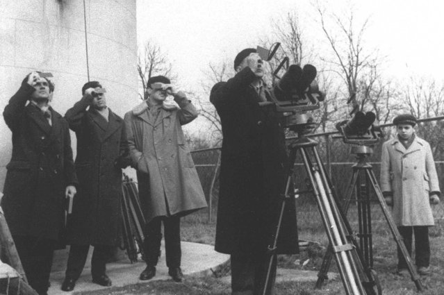Romanians observe a total eclipse of the sun through smoked pieces of glass in downtown Bucharest February 15, 1961. (Photo by AP Photo/ROMPRES)