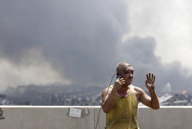 An injured man talks on his mobile phone at the site of the explosions at the Binhai new district in Tianjin August 13, 2015. (Photo by Jason Lee/Reuters)