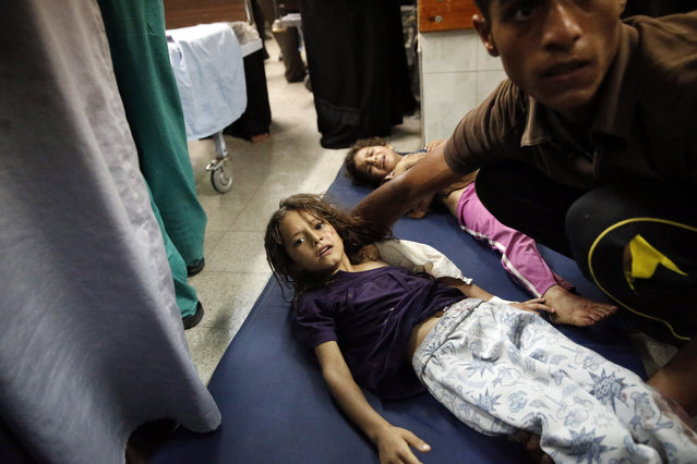 Palestinian children, wounded in an Israeli strike on a compound housing a U.N. school in Beit Hanoun, in the northern Gaza Strip, lay on the floor of an emergency room at the Kamal Adwan hospital in Beit Lahiya, Thursday, July 24, 2014. Israeli tank shells hit the compound, killing more than a dozen people and wounding dozens more who were seeking shelter from fierce clashes on the streets outside. (Photo by Lefteris Pitarakis/AP Photo)