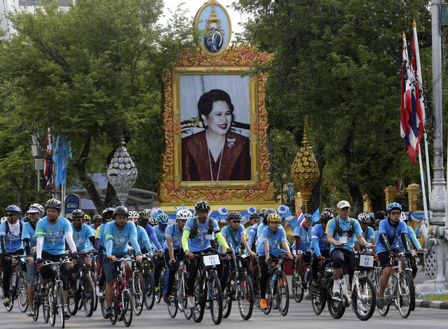 Cyclists pass by a portrait of Queen Sirikit in Bangkok, Thailand, Sunday, August 16, 2015. Thousands of cyclists pedaled through the streets of the Thai capital Sunday led by the country's crown prince on a 43-kilometer (26-mile) tribute to his mother, Queen Sirikit, to mark her 83rd birthday. (Photo by Sakchai Lalit/AP Photo)