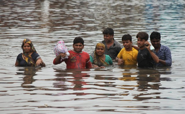 Indians wade through a waterlogged street in Ahmadabad, India, Wednesday, July 30, 2014. Normal life was thrown out of gear and rail and air traffic in several areas of Gujarat state were disrupted due to heavy rainfall, according to news reports. (Photo by Ajit Solanki/AP Photo)