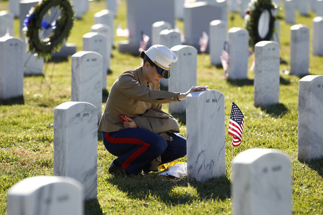U.S. Marine Capt. Jill A. Leyden of Easton, Maryland, touches the grave of her friend Major Megan M. McClung at Arlington National Cemetery in Virginia on Veterans Day, November 11, 2010. McClung was killed during Operation Iraqi Freedom on December 6, 2006. Leyden and McClung served together in Iraq. (Photo by Kevin Lamarque/Reuters)