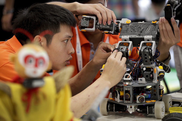 A college student fixes his robot to compete during the World Robot Conference at the Yichuang International Conference and Exhibition Centre in Beijing, Wednesday, August 23, 2017. (Photo by Andy Wong/AP Photo)