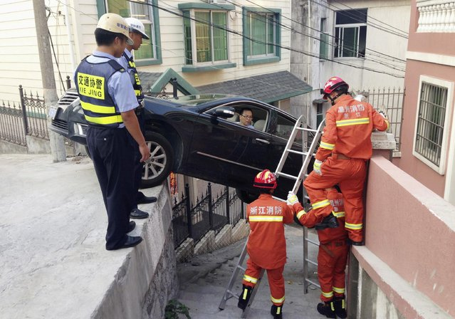 Rescue workers try to help a driver out of his car, after the vehicle was stuck over an alley in Wenzhou, Zhejiang province, August 4, 2014. The car rolled off the edge of a road after the driver was late to brake, according to local media. (Photo by Reuters/Stringer)
