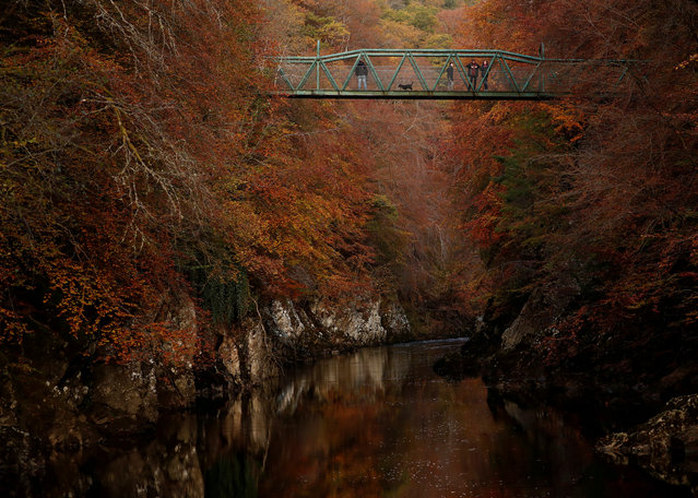People walk on the bridge over the river Garry, Pitlochry, Scotland, Britain on October 26, 2019. (Photo by Russell Cheyne/Reuters)
