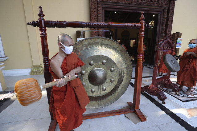 A Buddhist monk strikes a gong at a pagoda in Phnom Penh, Cambodia, Monday, Mar. 23, 2020. Buddhist pagodas in Cambodia on Monday offered prayer, chanting along with strikes of gongs and drums in hopes of chasing away the new coronavirus. (Photo by Heng Sinith/AP Photo)