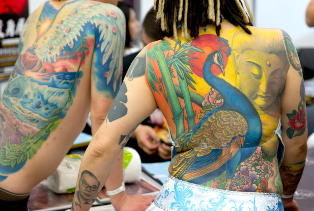 Iris (right) from Taiwan presents her tattoos at the international tattoo convention in Frankfurt am Main, Germany, on March 31, 2012. (Photo by Boris Roessler/AFP)