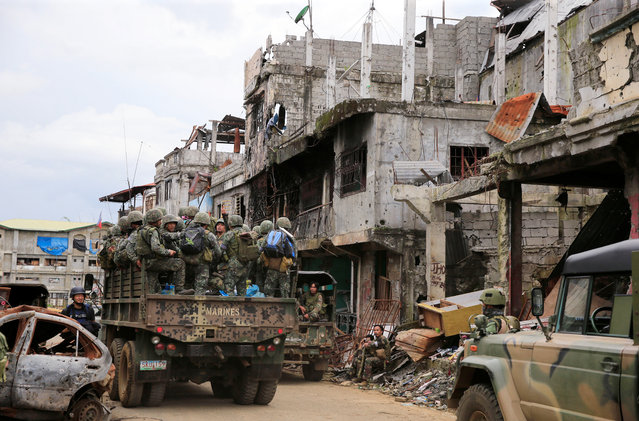 A military truck full of government soldiers move past damaged houses and buildings as troops continue their assault on clearing operations against the pro-IS militant group which seized Mapandi district in Marawi city, southern Philippines, September 13, 2017. (Photo by Romeo Ranoco/Reuters)