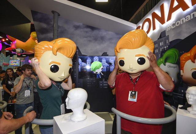 Fans try on plastic Conan O'Brien heads during Preview Night at Comic-Con International held at the San Diego Convention Center Wednesday July 20, 2016 in San Diego. (Photo by Denis Poroy/Invision/AP Photo)