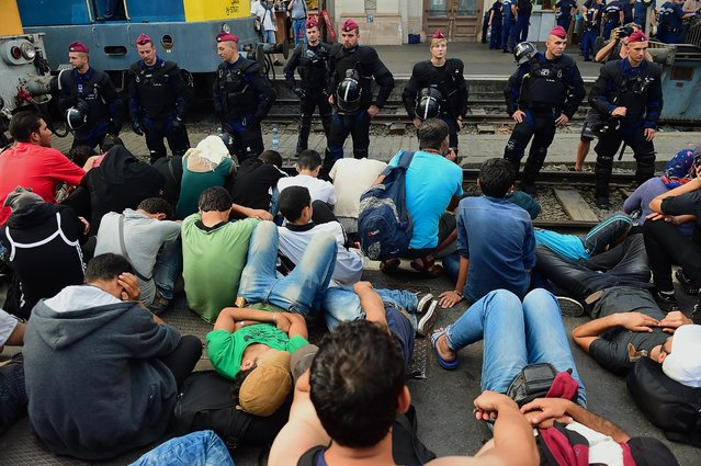 Riot police stand on the train track as they monitor migrants and refugees at the Keleti (eastern) railway station in Budapest on September 1, 2015. Keleti, the biggest Hungarian railway station was closed today as police evacuated people trying to get on trains bound for Germany. (Photo by Attila Kisbenedek/AFP Photo)
