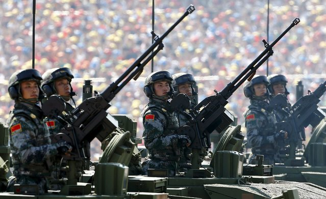 Soldiers of China's People's Liberation Army (PLA) hold guns while standing in armored vehicles during the military parade to mark the 70th anniversary of the end of World War Two, in Beijing, China, September 3, 2015. (Photo by Damir Sagolj/Reuters)
