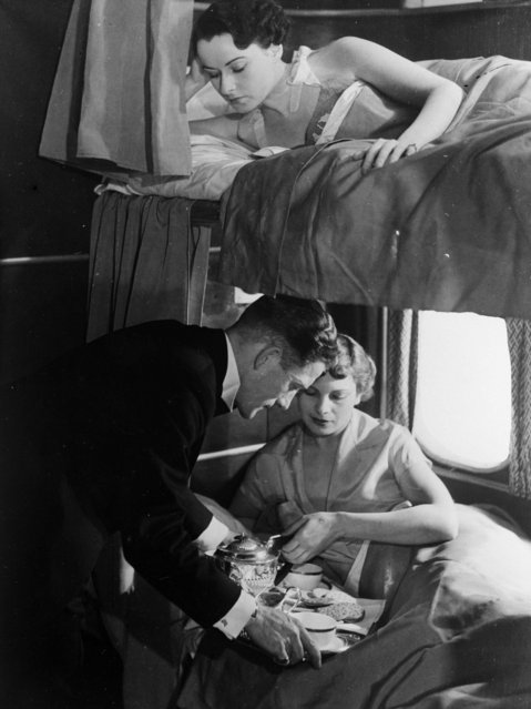 """A steward aboard the giant flying-boat, """"Canopus"""" serves breakfast to a passenger in a lower bunk while a woman in an upper berth waits, 1936. The Canopus belonging to Imperial Airways is on the Alexandria-Athens service. It can cruise at 200mph and carries 16 passengers in night stages. (Photo by General Photographic Agency/Getty Images)"""