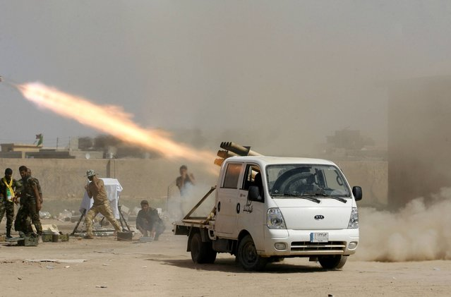 In this Wednesday, September 3, 2014 photo, Iraqi security forces and Shiite militiamen fire at Islamic State group positions during an operation outside Amirli, some 105 miles (170 kilometers) north of Baghdad, Iraq. (Photo by AP Photo/Stringer)