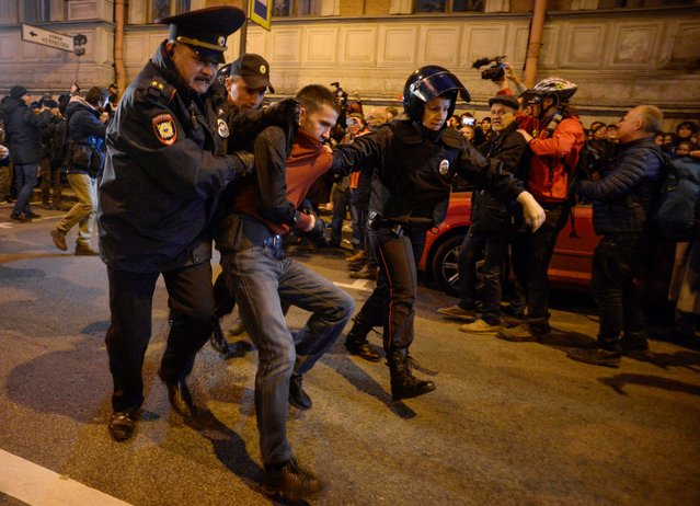 Russian police officers detain a supporter of opposition leader Alexei Navalny during an unauthorized rally in Saint Petersburg on October 7, 2017. Several thousand supporters of jailed opposition leader Alexei Navalny rallied across Russia on President Vladimir Putin's birthday on October 7, 2017, as police arrested more than 100 people. (Photo by Olga Maltseva/AFP Photo)