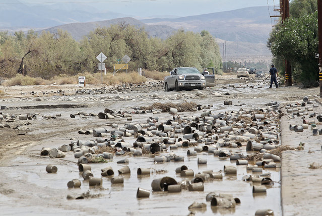 Plastic landscaping pots litter a road in Thousand Palms, Calif., after floodwaters surged Monday, September 8, 2014. (Photo by Jay Calderon/AP Photo/The Desert Sun)