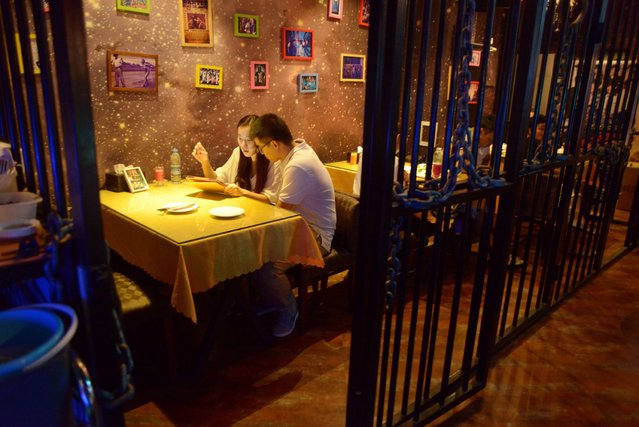 This picture taken on September 9, 2014 shows a couple preparing to have dinner at a prison themed restaurant in Tianjin. (Photo by Wang Zhao/AFP Photo)