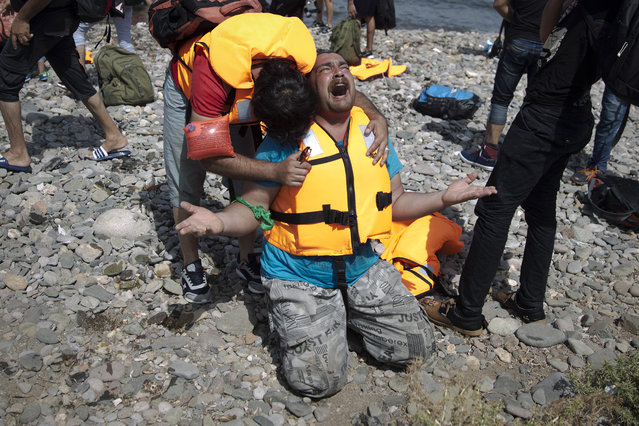 Syrian refugees react as they arrive after crossing aboard a dinghy from Turkey, on the island of Lesbos, Greece, Monday, September 7, 2015. The island of some 100,000 residents has been transformed by the sudden new population of some 20,000 refugees and migrants, mostly from Syria, Iraq and Afghanistan. (Photo by Petros Giannakouris/AP Photo)